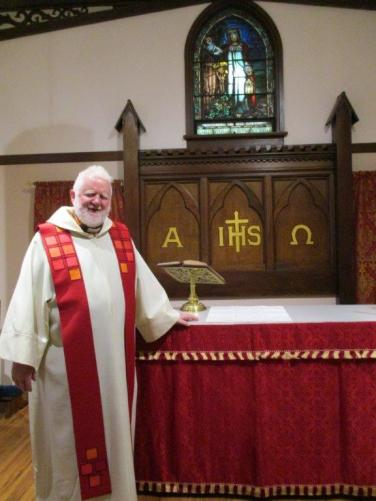 Image of Dean by the altar in the chapel.
