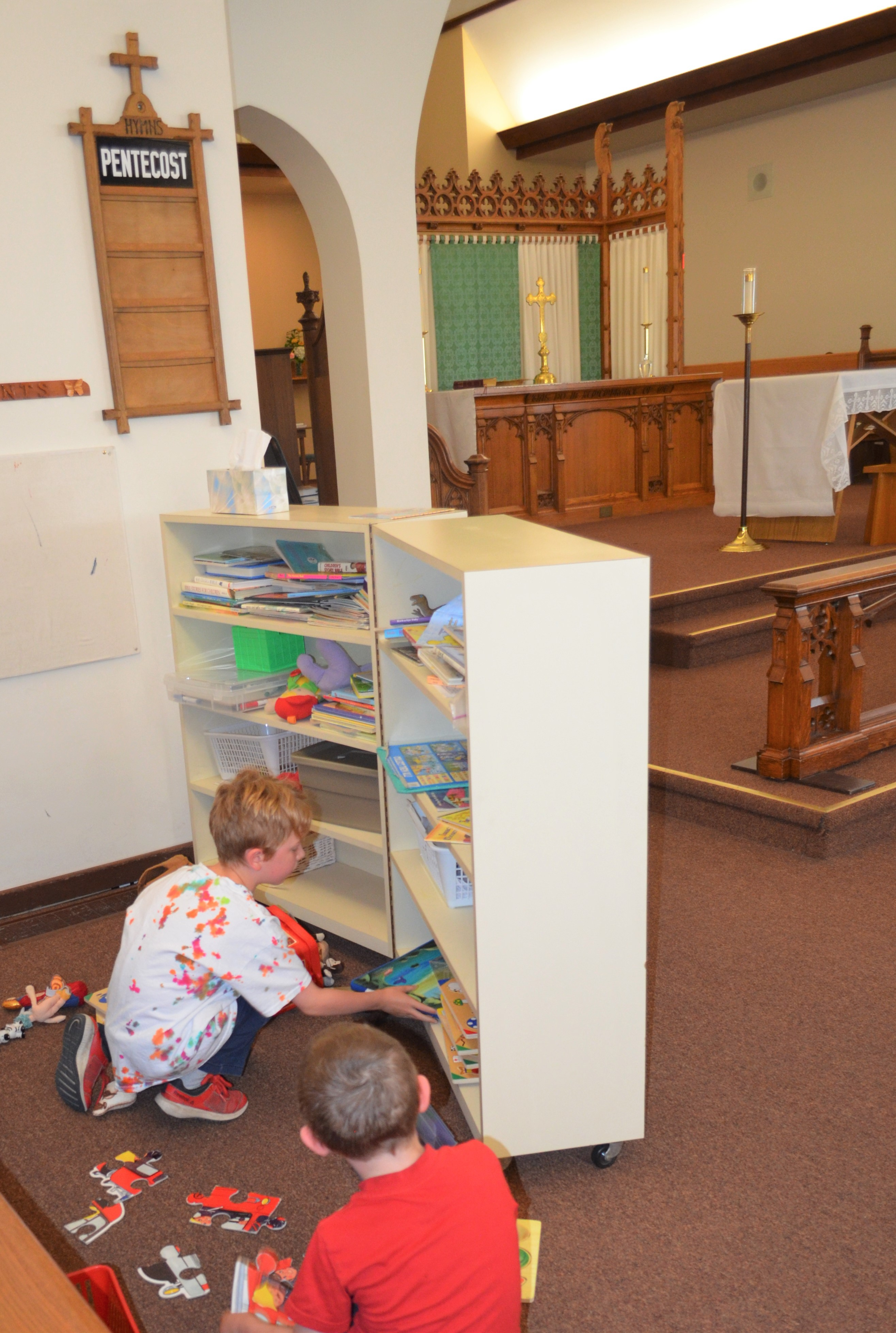 Two children playing with toys and books in the children's play area at the front of the church.