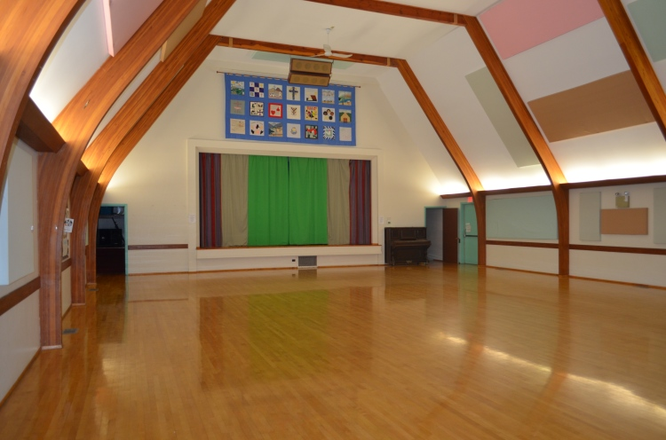 Bright community hall with wooden floors, vaulted ceiling and stage.